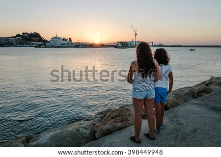 Girls looking at sunset from promenade - stock photo