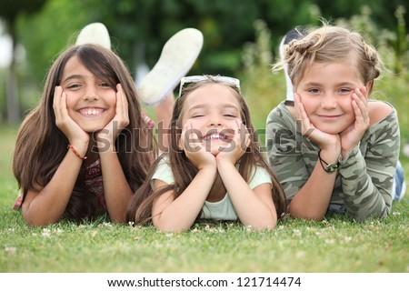 Girls lying on grass - stock photo