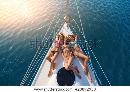 Girls lying on yacht. Smiling ladies wearing swimsuits. Have a happy summer. Today's weather is wonderful. - stock photo