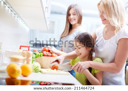 Girls making salad with their mother - stock photo