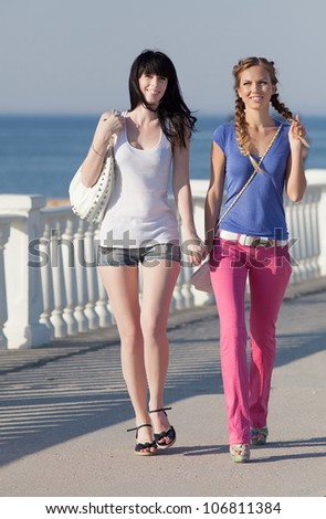 Girls on quay. Two attractive young women walking along seafront - stock photo