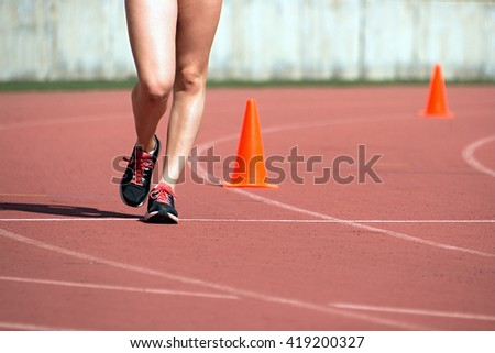 Girls on race walking on athletic track