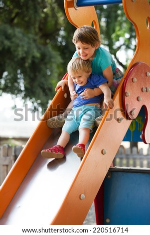 girls  on slide at playground area in summer