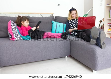 Girls on the couch with tablet and laptop - stock photo