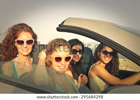 Girls on vacation driving a car - stock photo