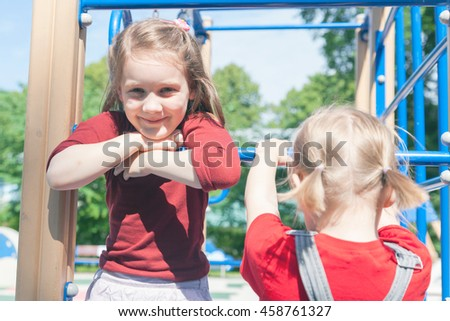 Girls playing on   playground in   summer.