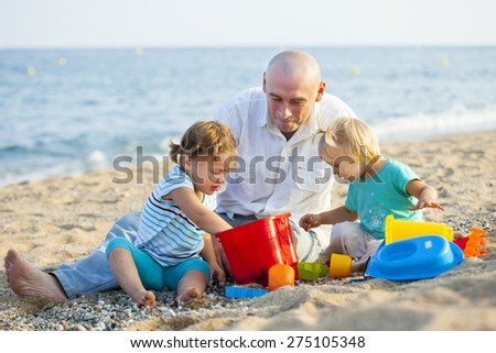 Girls playing with sand next to  father near sea. - stock photo