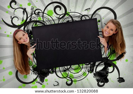 Girls pointing to black copy space with artistic black swirls and green paint splashes - stock photo