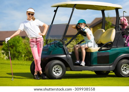 Girls posing near golf car in golf course at summer day - stock photo