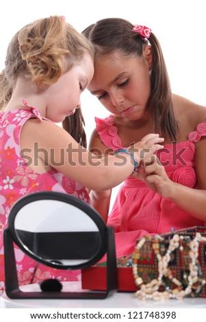 Girls putting on jewellery - stock photo