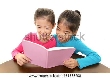 Girls reading a book - stock photo