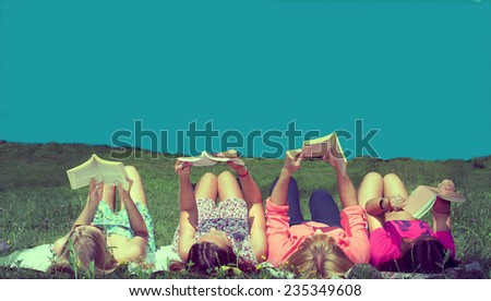 girls reading books lying on the meadow enjoying sunshine and blue sky in the summer time vintage look filtered image - stock photo