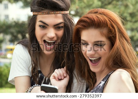 Girls reading message on mobile phone and smiling