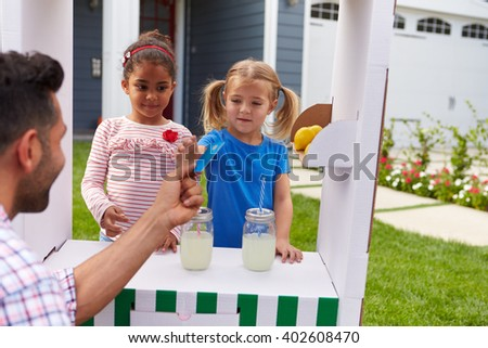 Girls Selling Homemade Lemonade From Stand At Home - stock photo