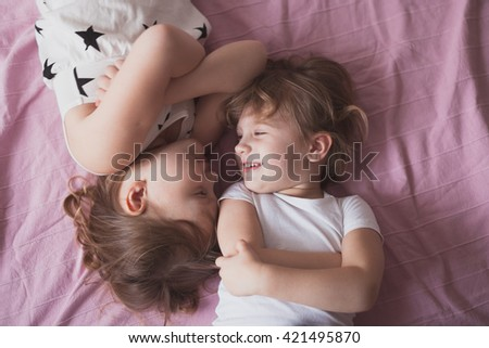 girls sisters siblings play, hug, relationships sisters, close up, domestic real situation, the concept of childhood, lifestyle,toning, - stock photo