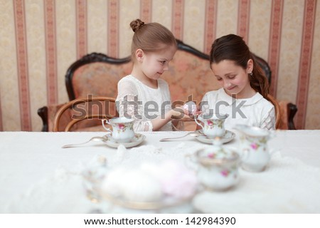 Girls sitting at the dinner table and drink tea from ceramic cups - stock photo