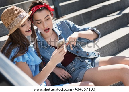 girls sitting on stairs with phone