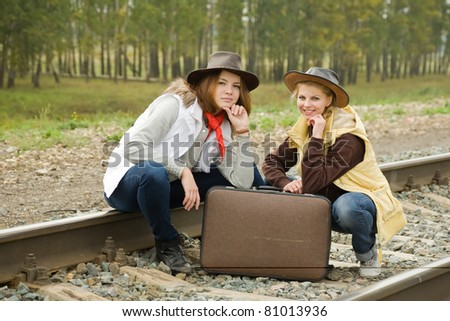 girls sitting with suitcase along the train tracks