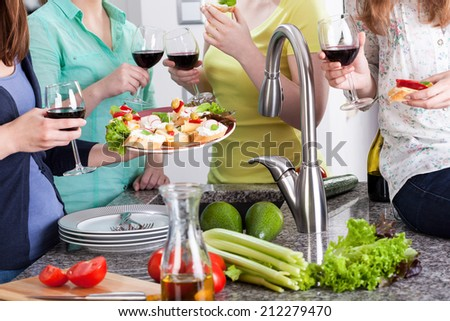 Girls spending time in kitchen, drinking wine and eating - stock photo