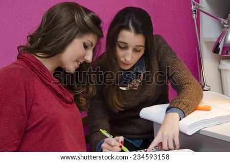 Girls studying together at home, one girl helps out another one, selective focus on a girl in foreground - stock photo