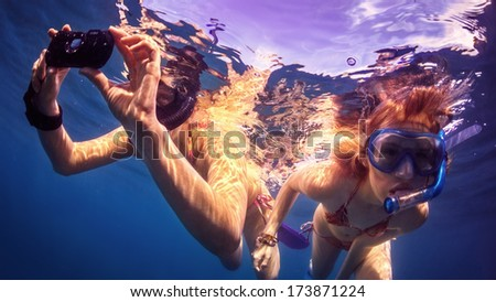 Girls swimming underwater with camera. - stock photo