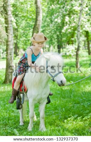 Girls take a walk with pony - stock photo