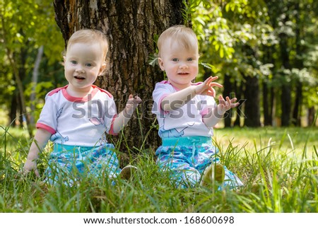 girls twins walk in the park in summer