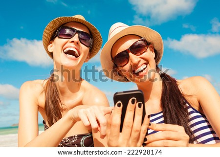 Girls using mobile phone on the beach. Summer holiday and technology concept - stock photo