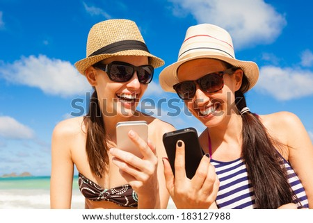 Girls using smart phone on the beach. Technology and beach concept. Summer holiday - stock photo