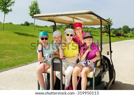 Girls walking in golf car at golf course at summer day