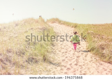 Girls walking up a dune path to the lake - stock photo