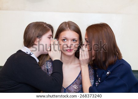 girls whispering to a friend - stock photo