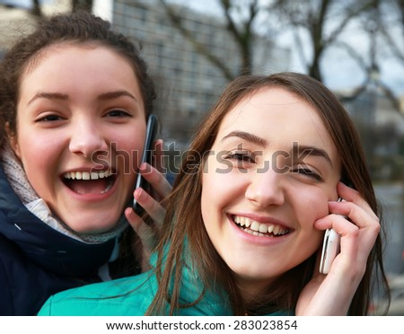 Girls with a mobile phones having fun outside - stock photo