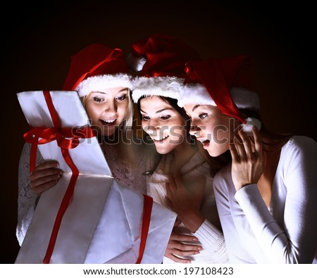 Girls with a new year gift on a dark background