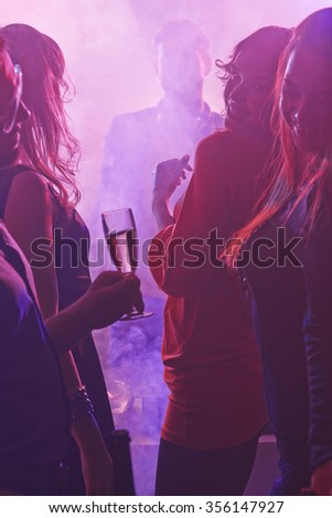 Girls with champagne flutes dancing at party