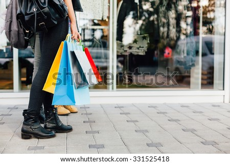 Girls with colorful shopping bags in front of shopping windows - stock photo