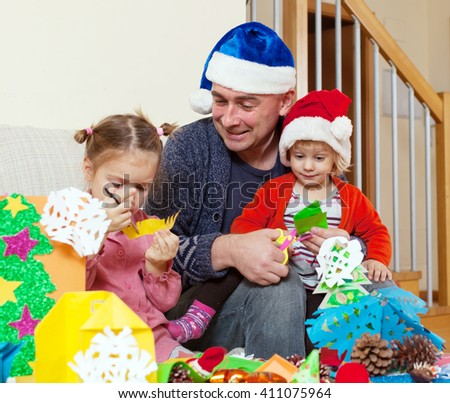 Girls with Dad on   couch doing holiday crafts.