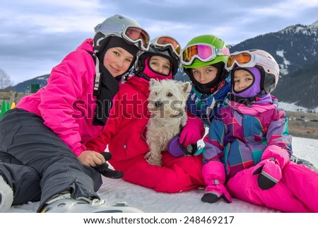Girls with dog on the ski vacation