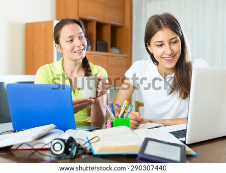 Girls with laptops and textbooks are preparing for graduation exam in school - stock photo