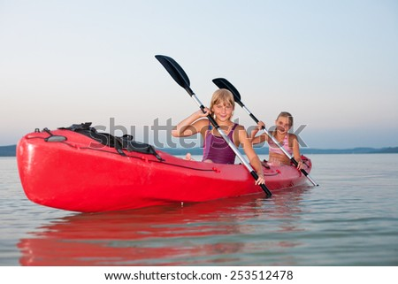 Girls with paddle and kayak on a lake at sunset - stock photo