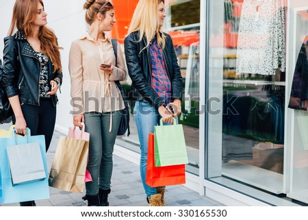 Girls with shopping bags delight are shopping windows