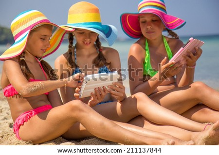 Girls with tablet on the beach - stock photo