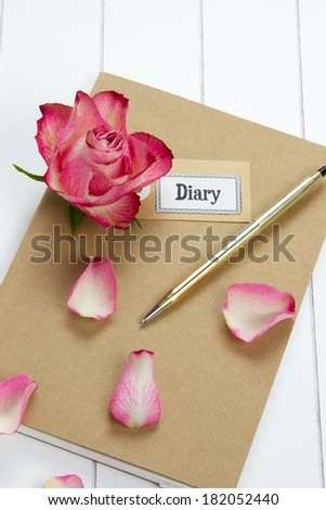 girly diary with red rose and leaves, pen and label tag on it - stock photo