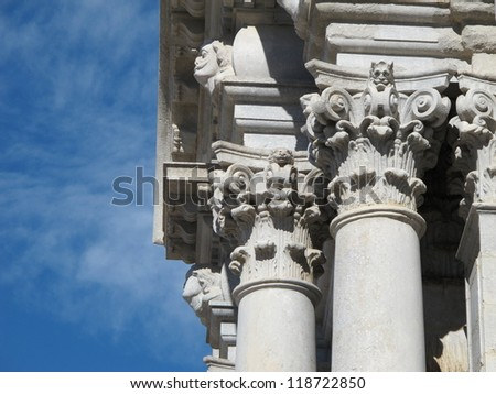 Girona corinthian white stone columns details on blue sky background - stock photo