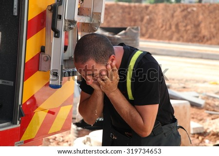 GIVAT SHMUEL, ISRAEL - JULY 29th, 2015: Brave firefighter washes his face after a long and difficult drill in hot weather