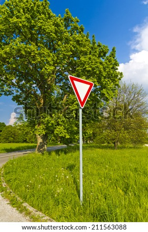 Give away traffic sign near trees and road