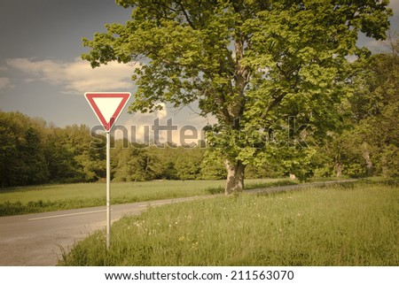 Give away traffic sign near trees and road, vintage style - stock photo