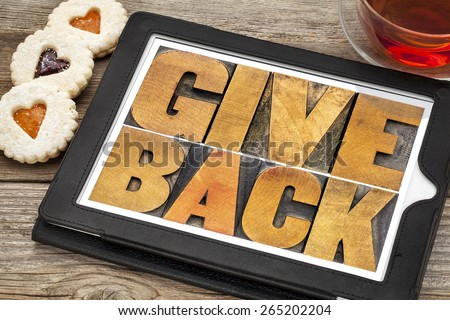 give back words text in letterpress wood type on a digital tablet with tea and heart cookies - stock photo