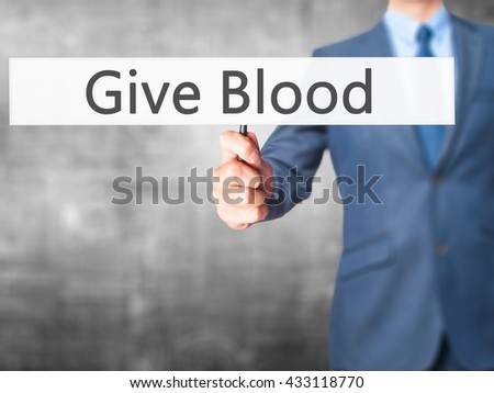 Give Blood - Businessman hand holding sign. Business, technology, internet concept. Stock Photo