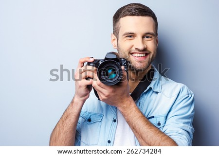 Give me a smile! Handsome young man holding digital camera and smiling while standing against grey background - stock photo